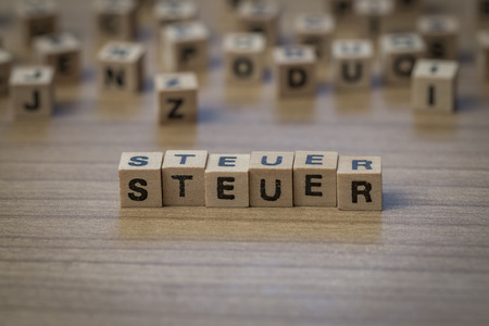 levy: Steuer (German Tax) written in wooden cubes on a table