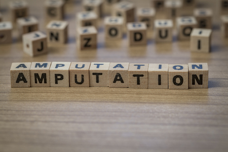 amputation: Amputation written in wooden cubes on a table Stock Photo