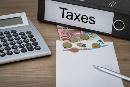 levy: Taxes written on a binder on a desk with euro money calculator blank sheet and pen