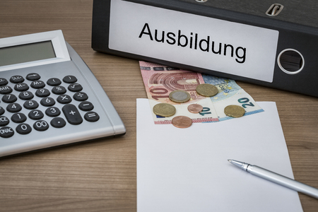 cost of education: Ausbildung (German education) written on a binder on a desk with euro money calculator blank sheet and pen Stock Photo