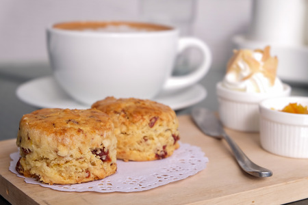 Traditional delicious British pastry and dessert - eating scones with hot latte coffee.