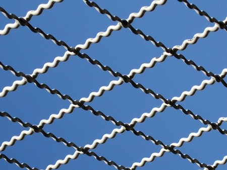 chainlink fence: iron wire fence on blue sky background  Stock Photo