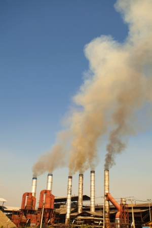 White Smoke out of Industrial smokestack blue background
