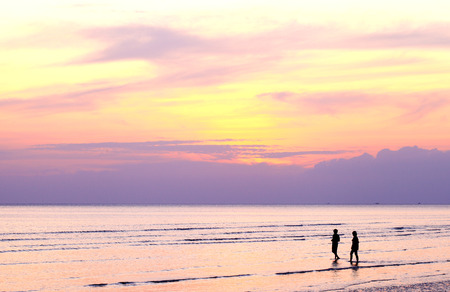 Silhouette two people walking along the beach when the sun sets.    Stock Photo