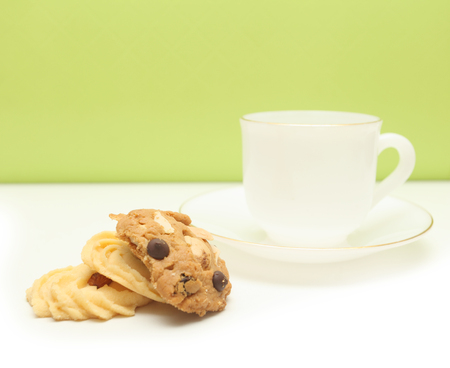 sweet cookie and white coffee cup green background Stock Photo