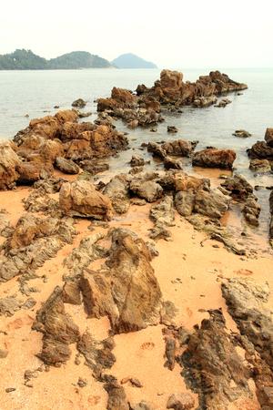 Large rocks coastline with waves crashing sea.