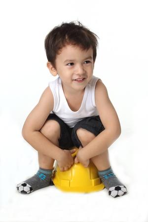 Future architect  Boy sitting on helmet isolated on white   Stock Photo
