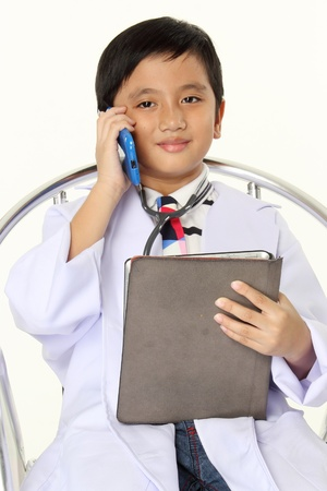 10 11 years: Future Doctor Smile on the face of a 10 year old boy dressed as a doctor holding Tablet and Mobile phone  Stock Photo