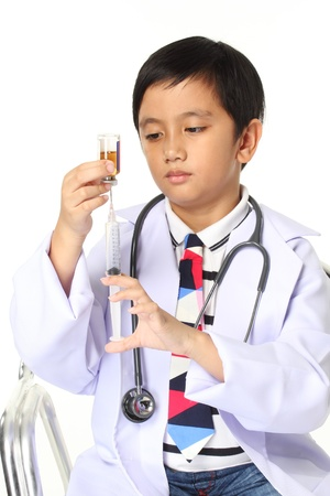 boy in big spectacles playing doctor with syringe and a stethoscope  Isolated over white   photo