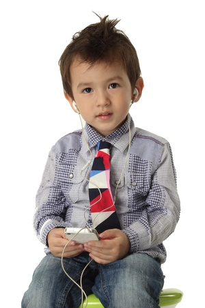 new age music: Music on smart phone Little boy listening to the music on smart phone   Stock Photo