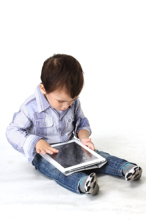 Sweet little boy sitting using a digital tablet   Stock Photo