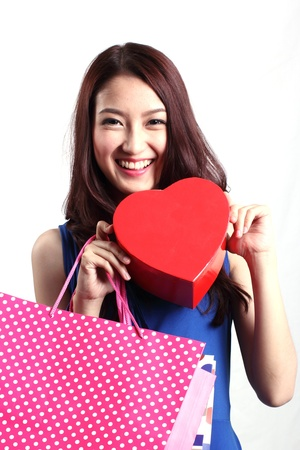 Closed up Asian woman carrying a chocolate box with the shape of a heart and shopping bag  photo
