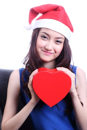 Closed up Asian woman with a christmas hat and carrying a chocolate box with the shape of a heart  photo