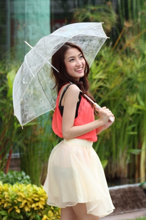 Happy Asian young woman standing with a white umbrella photo