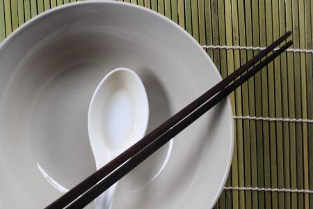 bamboo mat: A place setting for an asian dish against bamboo mat