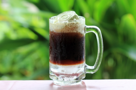 Root beer float, a tasty summer treat on Green tree background