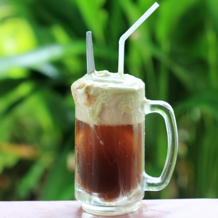 float: Root beer float, a tasty summer treat on Green tree background  Stock Photo
