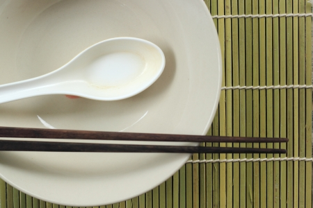 A place setting for an asian dish against bamboo mat photo