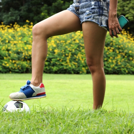 teenage soccer playing girl resting with her foot on the soccer ball photo