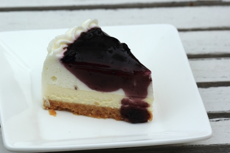 delectable: slice of delectable cheescake with a blueberry glaze topping  Stock Photo