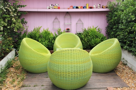 Rattan furniture on lawn in a green garden photo
