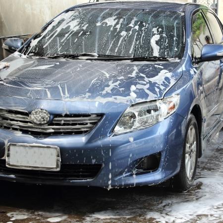 laver main: laver une voiture bleue avec une mousse et d'eau