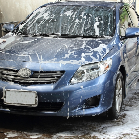 washing a blue car with a foam and water photo