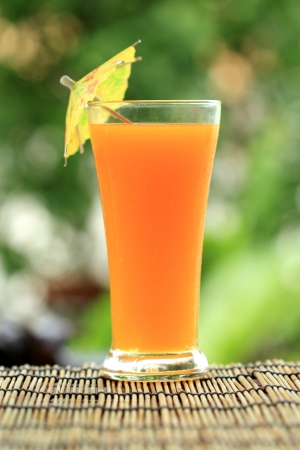 Glass of of orange juice on garden background  photo