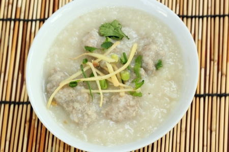 Traditional chinese porridge rice gruel in bowl with pork photo