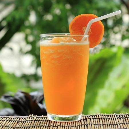 Glass of Orange Smoothie on garden background  Stock Photo
