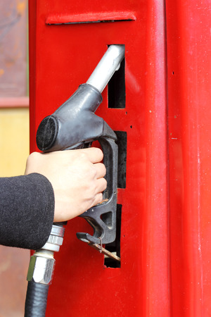 hand of male holding a fuel pump at gasoline station  photo