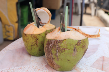 Two Fresh coconut with spoon and straw   selective focus photo