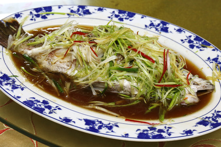 Seabass fish steamed with soy sauce and vegetable topping photo