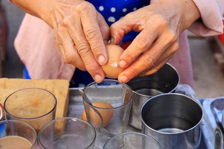 Female cracks open soft boiled egg into glass photo
