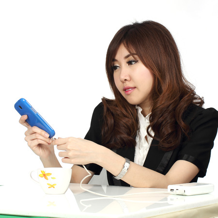 Young attractive Asian businesswoman charging her mobile phone isolated on white background   photo
