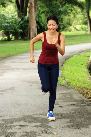 Asian woman running in park in sunshine on the holiday photo