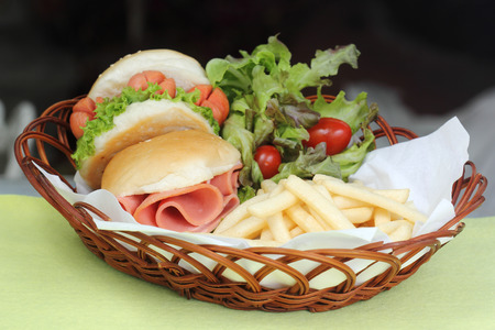 freshly Hamburger in a basket with freshly cooked Potato fries and vegetable photo
