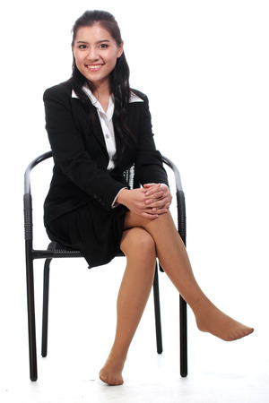 Asian business woman sitting on a chair   isolated on white background photo