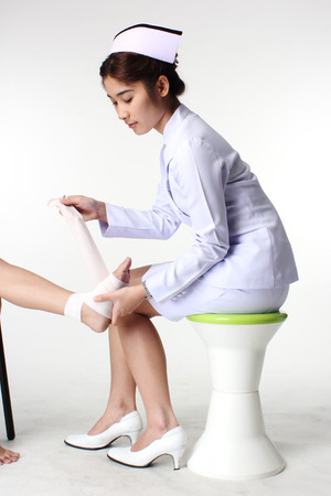 Nurse bandaging patient Isolate on white  photo