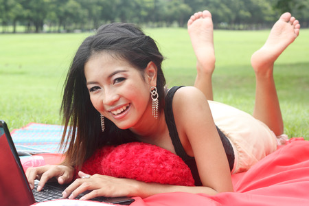Young woman lying on red mat in park and using laptop photo