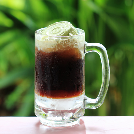 Root beer float a tasty summer treat on Green tree backgroun photo