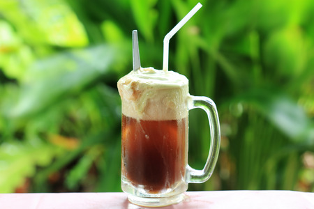Root beer float a tasty summer treat on Green tree background photo