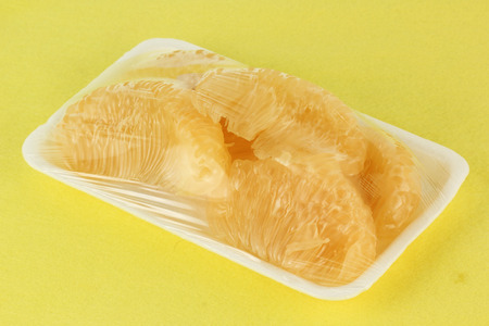 Slice of Grapefruit packed in foam tray with plastic wrap photo