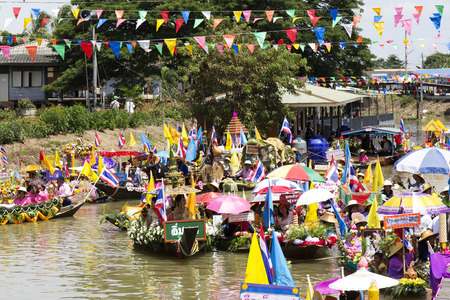 AYUTTHAYA, THAILAND - JULY 11: Unidentified people on flower boats in floating parade, the unique annual candle festival of Buddhist lent on July 11, 2014 in Ladchado, Ayutthaya, Thailand