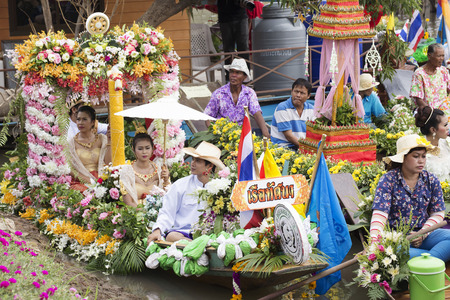 AYUTTHAYA, THAILAND - JULY 11  Unidentified people on flower boats in floating parade, the unique annual candle festival of Buddhist lent on July 11, 2014 in Ladchado, Ayutthaya, Thailand