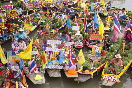 AYUTTHAYA, THAILAND - JULY 11  Unidentified people on flower boats in floating parade, the unique annual candle festival of Buddhist lent on July 11, 2014 in Ladchado, Ayutthaya, Thailand Editorial
