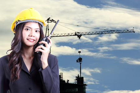 Engineer woman talking with a walkie talkie at Construction site  photo