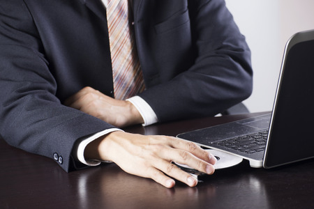Hand of Business man holding Disk insert to laptop computer photo