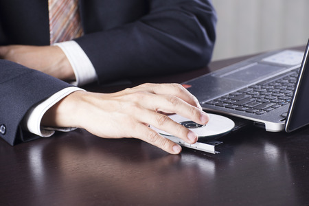 Hand of Business man insert disk to laptop computer Stock Photo