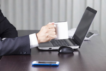Close up hand of Businessman holding cup of coffee photo